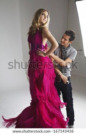 Male designer adjusting dress on fashion model in studio - stock photo