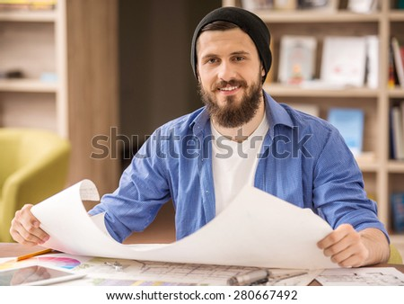 Male designer dressed casual sitting at the table and holding whatman paper at home office.
