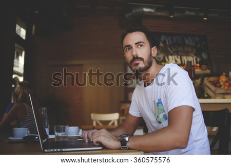 Male developer comes up with ideas for website while sitting front open laptop computer in cozy restaurant interior, young man thinking about something during work on net-book in modern coffee shop - stock photo