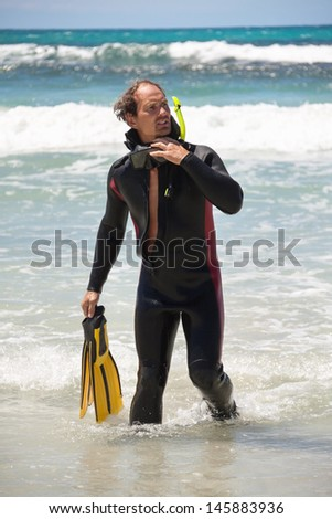 male diver with diving suit snorkel mask fins on the beach in Summer - stock photo