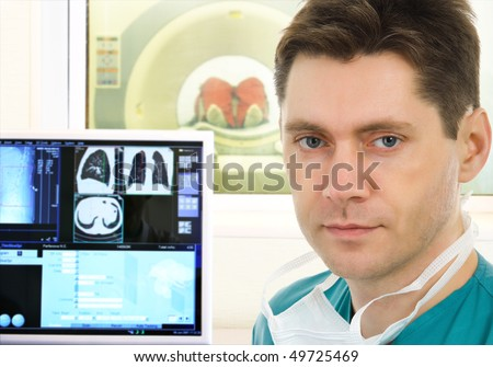 Male doctor and computer tomographic scanner in hospital - stock photo