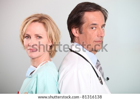Male doctor and female nurse - stock photo