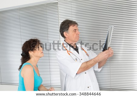 Male Doctor and female Patient Discuss  (Xray)  - stock photo