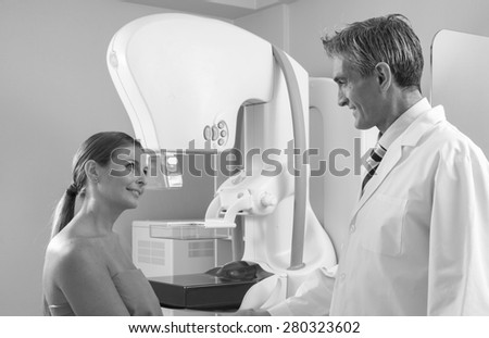 Male doctor and female patient shaking hands in the hospital room. - stock photo