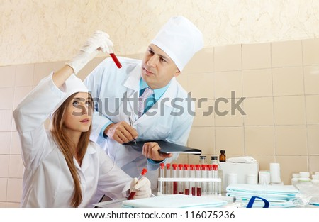 Male doctor and nurse with test tubes makes blood test in medical laboratory - stock photo