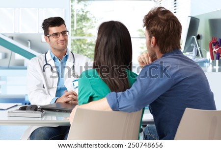 Male doctor consulting with young couple in doctor's room. - stock photo