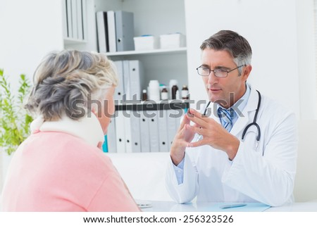 Male doctor discussing with female patient wearing neck brace in clinic - stock photo