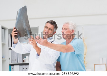 Male doctor discussing with male patient over x-ray in clinic - stock photo