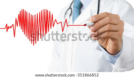 Male doctor drawing heart symbol at the whiteboard - stock photo