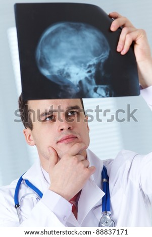 Male doctor examines  X-ray picture of a human cranium - stock photo