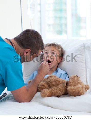 Male doctor examining child throat in hospital - stock photo