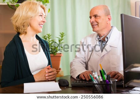 Male doctor examining  mature female patient in clinic - stock photo