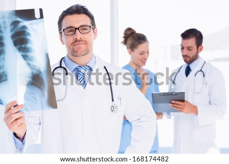 Male doctor examining x-ray with colleagues in the background at medical office - stock photo