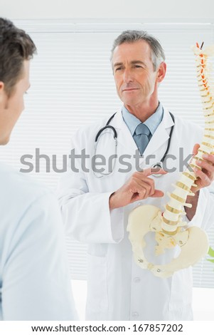 Male doctor explaining the spine to a patient in medical office