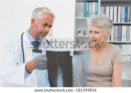 Male doctor explaining x-ray to senior patient in the medical office - stock photo