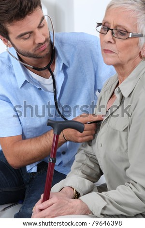 Male doctor giving elderly woman medical check-up - stock photo