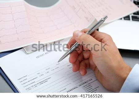 Male doctor hands with cardiogram chart on clipboard pad fill medical history with silver pen. Cardio therapeutist assistance, physician make cardiac physical, pulse measure document, arrhythmia idea