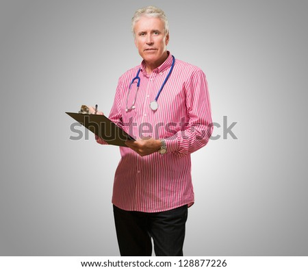 Male Doctor Holding Writing Pad against a grey background - stock photo