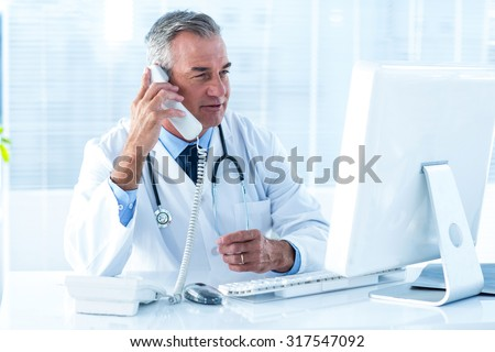Male doctor in conversation through telephone while looking at computer in hospital - stock photo