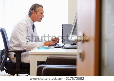 Male Doctor In Office Working At Computer - stock photo