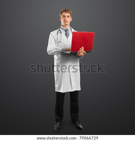 male doctor in suit with laptop in his hands, looking on camera - stock photo