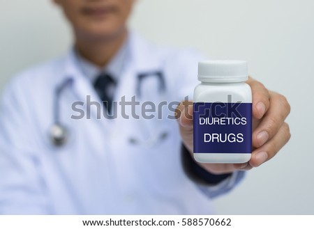 Male doctor in white uniform holding blue label white bottle of diuretics drugs, close up
