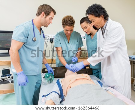 Male doctor instructing nurses to insert endotracheal tube in dummy patient's mouth in hospital room - stock photo