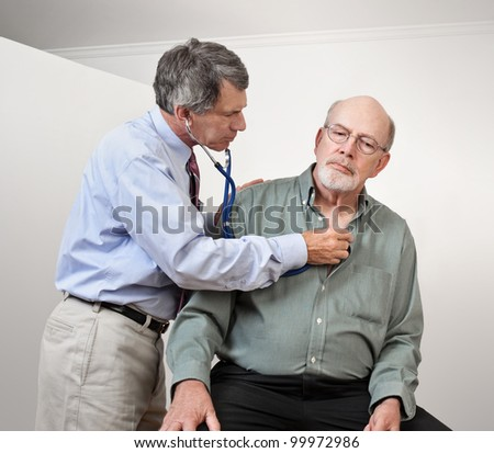 Male doctor listening to older man's heart with stethoscope - stock photo