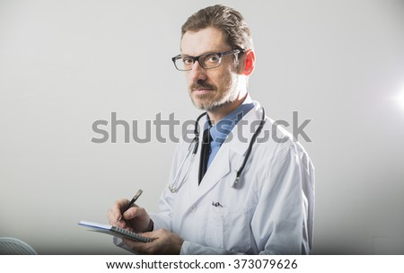 male doctor makes notes of the diagnosis and looking at the viewer - stock photo