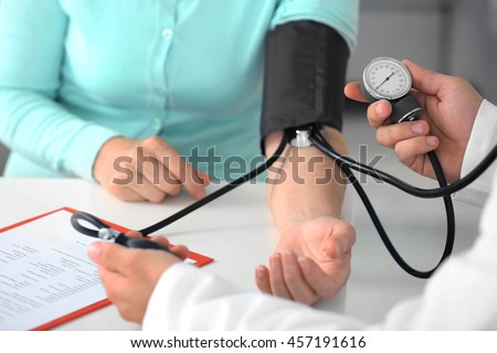 Male doctor measuring woman blood pressure with tonometer