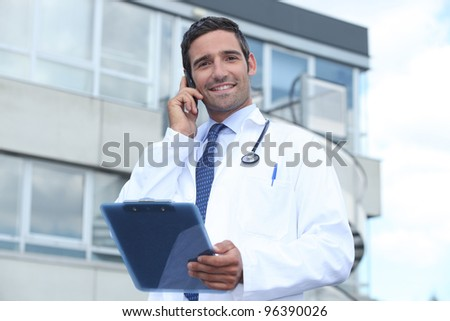 Male doctor outside hospital making phone call - stock photo