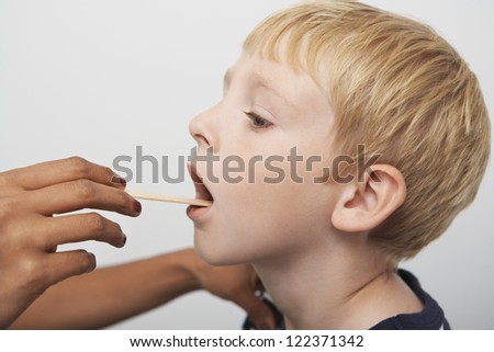 Male doctor's hand examining boy's throat in clinic