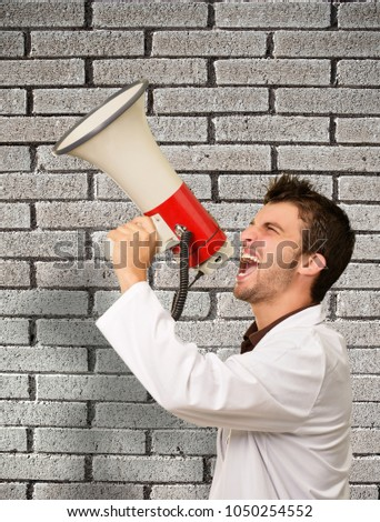 Male Doctor Shouting In Megaphone Against Wall