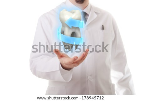 Male doctor showing a molar tooth - stock photo