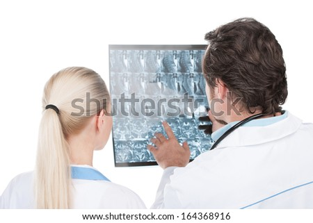 Male doctor showing his female assistant roentgen of patient. Back view isolated on white.  - stock photo