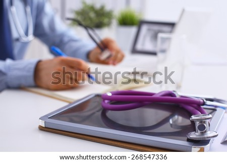Male doctor sitting at his desk - stock photo
