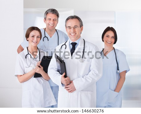 Male Doctor Standing In Front Of Team Using Digital Tablet