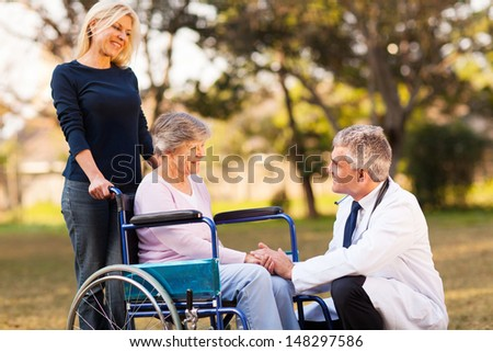 male doctor talking with handicapped senior woman at the retirement home - stock photo