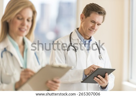 Male doctor using digital tablet with female colleague holding clipboard in foreground at hospital