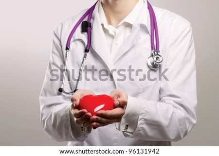 Male doctor with stethoscope holding heart on grey  background.