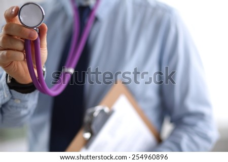 Male doctor with stethoscope listening something - stock photo