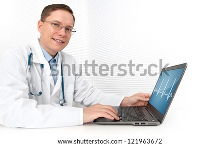 male doctor working on a laptop. heart beats cardiogram - stock photo