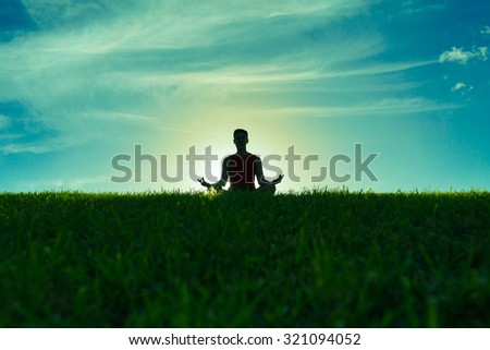 Male doing yoga in a grass field.  - stock photo
