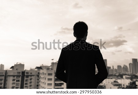 Male dressed in a suit looking out into the big city.  - stock photo
