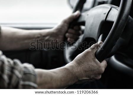 Male driver hands holding steering wheel. - stock photo