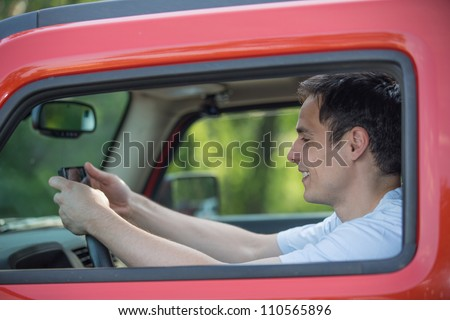 Male Driver Holding Cellphone Texting by Wheel Driving - stock photo
