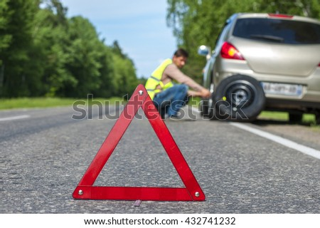 Male driver in reflective vest changing tire after breakdown. Focus on red warning triangle sign. - stock photo