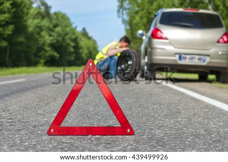 Male driver in reflective vest with spare wheel on the roadside, broken car and red triangle warning sign. Focus on red sign - stock photo