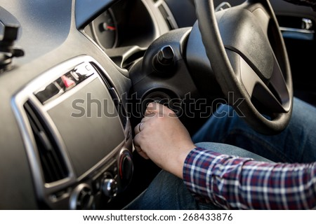 Male driver turning ignition key in right-hand drive car - stock photo