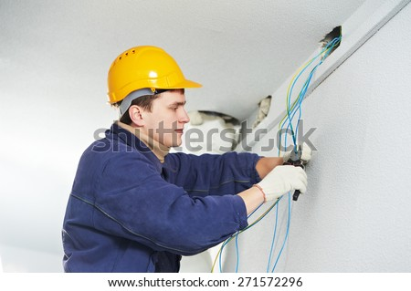 Male electrician at work laying wiring cable - stock photo